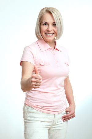 average age: Smilling attractive middle aged woman showing thumbs up, okay. Isolated square