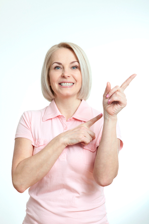 average age: Friendly smiling middle aged woman pointing at copyspace isolated on white background
