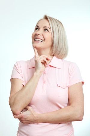 Mittlere gealterte schöne Frau denken nachschlagen und Träumen auf weißem Hintergrund