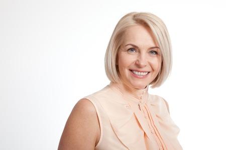 Vriendschappelijke glimlachende vrouw van middelbare leeftijd op een witte achtergrond Stockfoto