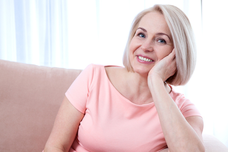 dientes sanos: hermosa mujer de mediana edad activa sonriendo amable y mirando a la cámara. Primer de la cara de la mujer.