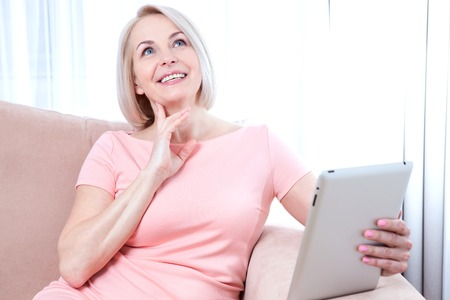 beautiful middle aged woman: Smiling beautiful middle aged woman sitting on couch with tablet, considering new idea. Stock Photo