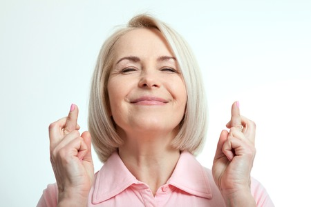 Closeup portrait hopeful beautiful woman crossing her fingers, eyes closed, hoping, asking best isolated on white wall background. Human face expression, emotions, feeling attitude reaction