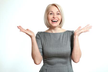 Kobieta szuka zaskoczony. Przyjazny uśmiechnięta kobieta w średnim wieku na białym tle