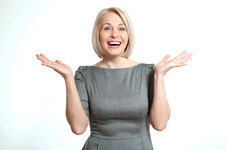 Mujer mirando sorprendido. Amistoso sonriente mujer de mediana edad aisladas sobre fondo blanco