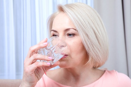 beautycare: Portrait beautiful middle aged woman drinking water in the morning. Womans face close up Stock Photo