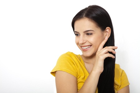 Close up candid portrait of young woman laughing against white background