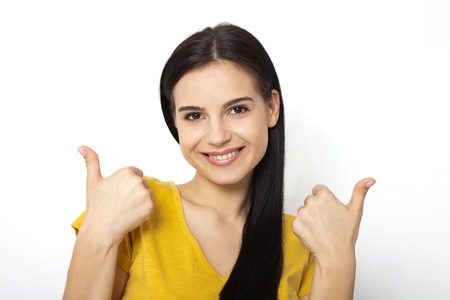 Happy attractive young woman showing thumbs up, okay close up. Isolated Stock Photo