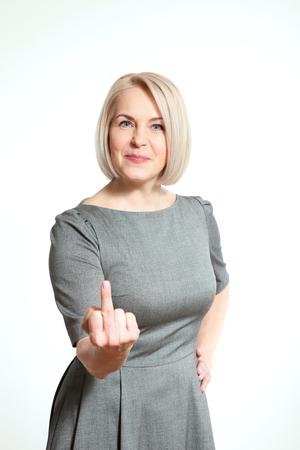 De vrouw toont teken van Fuck Off. Sexy vrouw van middelbare leeftijd blijkt middelste vinger in het gezicht met een grimas close-up. professionele make-up