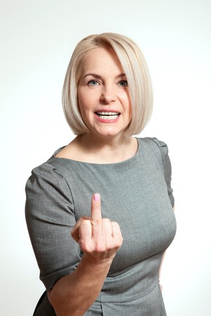 fuck: Woman shows sign of fuck off. Sexy middle aged woman showing middle finger in face with a grimace closeup. Professional makeup