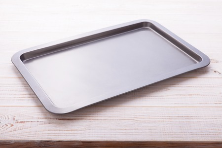 Empty baking tray on white wooden desk close up top view horizontally.