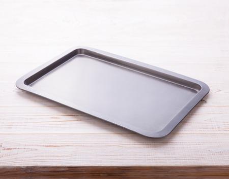 horizontally: Empty baking tray on white wooden desk close up top view horizontally.