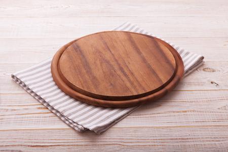 tablero de pizza con una servilleta en mesa de madera blanca. Vista superior maqueta