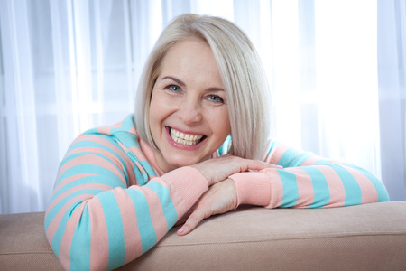 average age: Attractive middle aged woman relaxing at home. The beautiful face close up.
