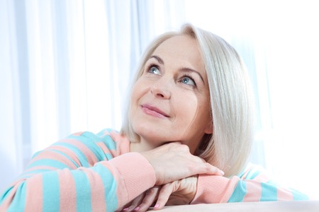 Attractive middle aged woman looking up relaxing at home. Beautiful face close up. Stock Photo