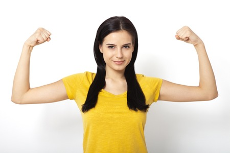 muscularity: Strong woman. Beautiful young woman showing her muscularity and looking at camera while isolated on white Stock Photo