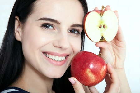 Woman with apple close-up face. Beautiful women exists to clean skin on the face. Asian woman. Stock Photo