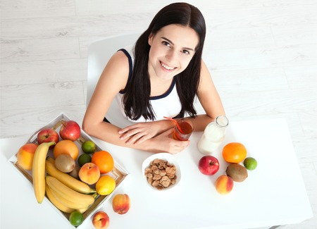 Beautiful women exists with pure skin on her face sitting at a table and eat breakfast. Asian woman eating healthy food at breakfast. Fruit, cereal and milk. Stock Photo