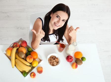 美しい女性は、テーブルに座って彼女の顔には純粋な皮膚の存在し、朝食を食べる。アジアの女性は、朝食で健康的な食生活。フルーツ、シリアル