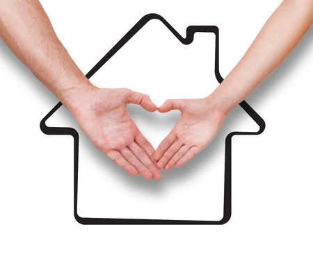 Real estate, family and couple concept Couple making heart shape made with their fingers. Drawing house as a background isolated on white. Stock Photo