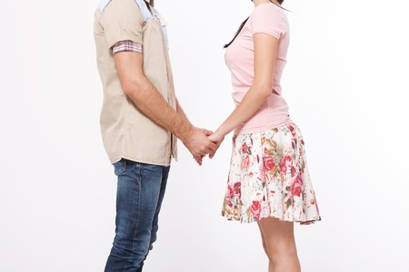 Young couple in love holding hands isolated on white background