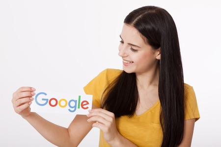 Kiev, Ukraine - August 22, 2016: Woman hands holding Google logotype printed on paper on grey background.Google is USA multinational corporation.