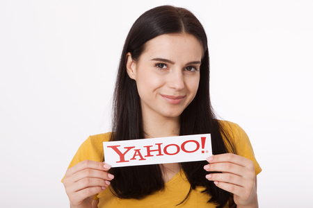 Kiev, Ukraine - August 22, 2016: Woman hands holding the logo of the brand Yahoo icons printed on paper on grey background.