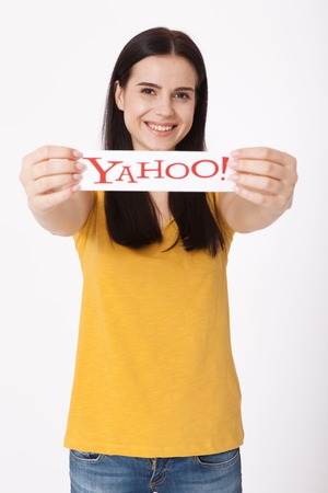 yahoo: Kiev, Ukraine - August 22, 2016: Woman hands holding the logo of the brand Yahoo icons printed on paper on grey background.
