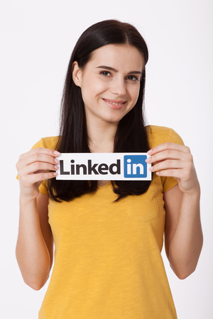 KIEV, UKRAINE - August 22, 2016: Woman hands holding Linkedin logo sign printed on paper on white background. Linkedin is business social networking service.