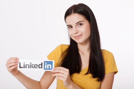 social networking service: KIEV, UKRAINE - August 22, 2016: Woman hands holding Linkedin logo sign printed on paper on white background. Linkedin is business social networking service.