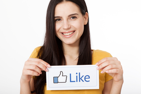 social networking service: KIEV, UKRAINE - August 22, 2016: Woman hands holding facebook thumbs up sign printed on paper on white background. Facebook is well-known social networking service.