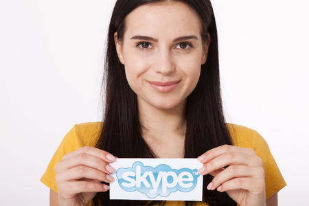background skype: KIEV, UKRAINE - August 22, 2016: Woman hands holding Skype logotype printed on paper on grey background. Skype is a telecommunications application software developed by Microsoft.