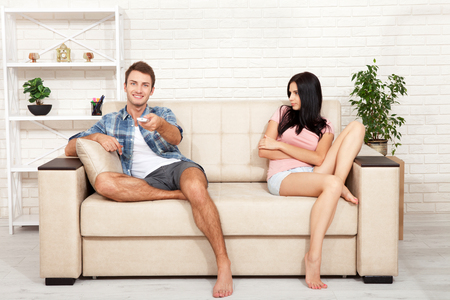 Dissapointed beautiful brunette woman in quarrel with her boyfriend. Indifferent man watching TV.