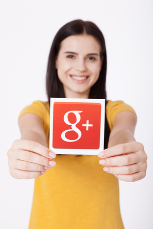 gmail: Kiev, Ukraine - August 22, 2016: Woman hands holding Google plus icon printed on paper on grey background.Google is USA multinational corporation. Editorial