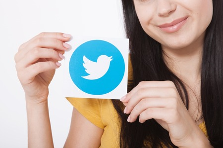enables: KIEV, UKRAINE - AUGUST 22, 2016: Woman hands holding Twitter logotype icoi bird printed paper. Twitter is an online social networking service that enables users to send and read short messages. Editorial