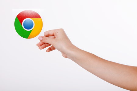gmail: Kiev, Ukraine - August 22, 2016: Woman hands holding Google Chrome icon printed on paper on grey background.Google is USA multinational corporation. Editorial