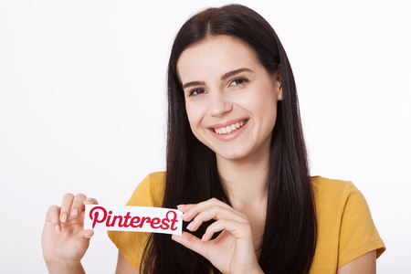 KIEV, UKRAINE - AUGUST 22, 2016: Woman hands holding Pinterest ilogotype con printed paper. Is photo sharing website. Editorial