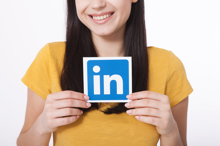 KIEV, UKRAINE - August 22, 2016: Woman hands holding Linkedin icon sign printed on paper on white background. Linkedin is business social networking service.