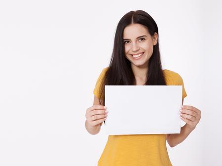 Tu texto aqui. Bastante joven mujer celebración vacío tablero en blanco. Retrato del estudio en el fondo blanco. Maqueta para el diseño