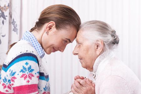 Handhulp, zorg voor het oudere concept Senior en verzorger houden handen thuis Stockfoto