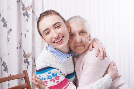 Helping hands, care for the elderly concept. Senior and caregiver holding hands at home Stock Photo