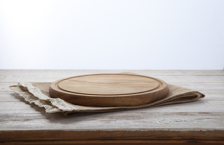 Pizza board, canvas napkin with lace on wooden table. Top view mock up Foto de archivo