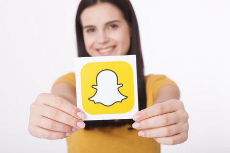 Kiev, Oekraïne - 22 augustus 2016: Vrouw handen met Snapchat logo pictogram afgedrukt op papier. Snapchat is een populaire toepassing voor sociale media voor het delen van berichten, afbeeldingen en video's