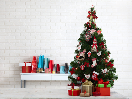 White wooden table in front of colorful christmas tree with gift boxes. Can be used for display or montage your products Stock Photo