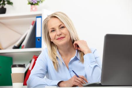 Il suo lavoro è la sua vita. Donna d'affari, lavorando in ufficio con documenti. Donna invecchiata bello mezzo che esamina macchina fotografica con il sorriso mentre ubicazione nell'ufficio.