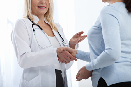 Healthcare and medical concept - doctor with patient in hospital. Handshake. Stock Photo
