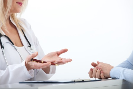 Doctor and patient are discussing something, just hands at the table close up