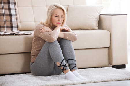 Middle aged barefoot woman sitting at the floor embracing her knees, near sofa at home, her head down, bored, troubled with domestic violence.
