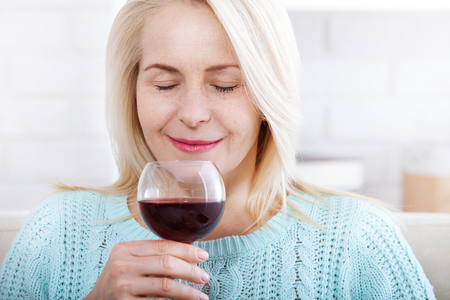 Happy blonde drinking red wine with eyes closed.