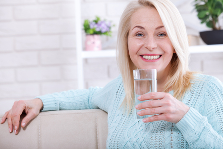 Beautiful middle aged woman drinking water in the morning